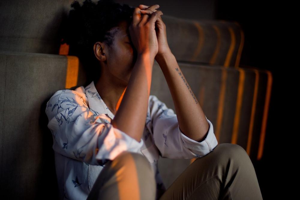 pessoa estressada sentada no chão com as mãos no rosto