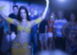Aline Mesquita. Bailarina de Dança do Ventre vestindo um figurino amarelo dança em uma festa com os braços para cima enquanto público ao fundo assiste.