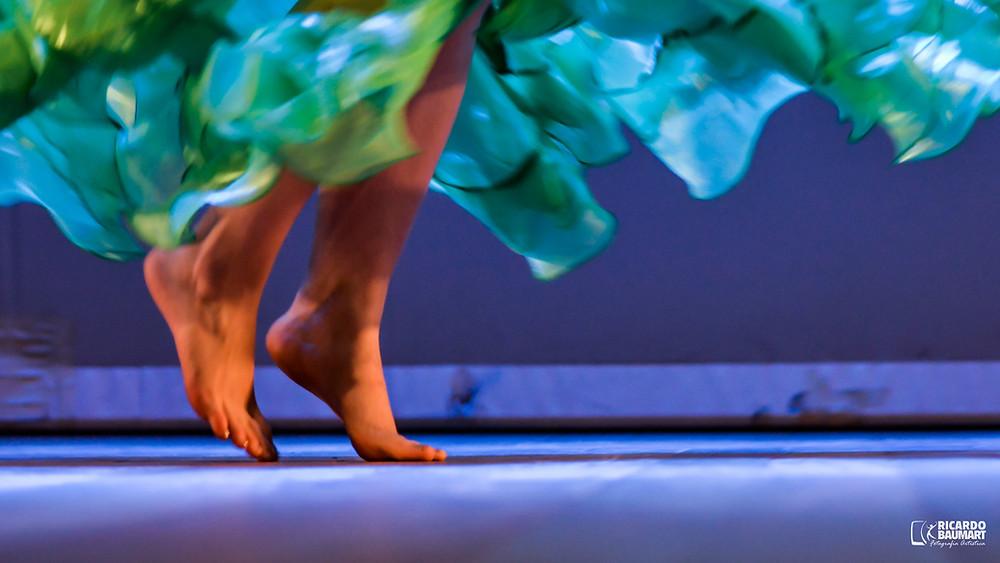 descalços, os pés da bailarina Aline Mesquita gentilmente tocam o solo do palco em uma apresentação de dança do ventre