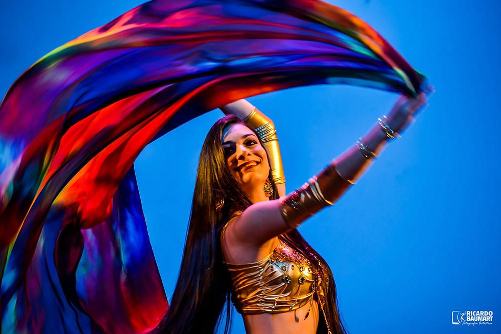 Aline Mesquita em apresentação de dança do ventre com véu colorido e figurino dourado.