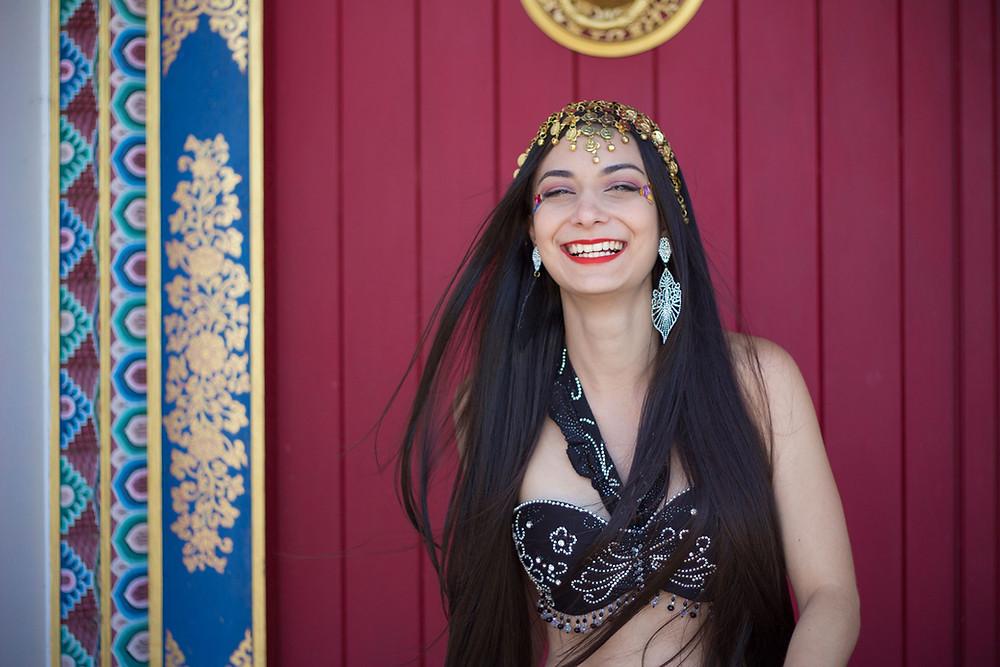 Aline Mesquita com largo sorriso no rosto. Ela está com figurino preto de dança do ventre, um enfeite dourado na cabeça e grandes brincos prateados detalhados como se fossem folhas; o cabelo parece balançar com o vento. Ao fundo uma porta vermelha com detalhes coloridos em volta.