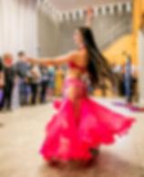 Aline Mesquita. Bailarina de Dança do Ventre usa um figurino rosa cintilante e dança graciosamente com público ao fundo tirando fotos
