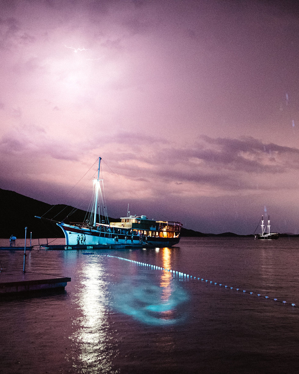 Lightning over a boat in Tisno Bay the Garden At Love International Festival. Events, Festival Tisno, Music Photography. Photo taken by Rob Jones @hirobjones