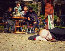 A Japanese street artist lying on the ground and watching a turtle in Zenpukuji Park