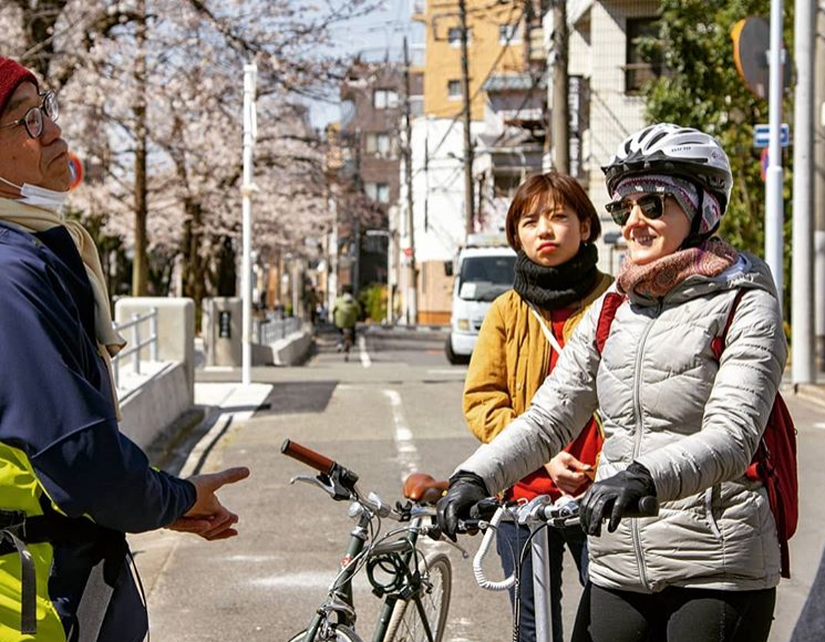 A bicycle tour guide talking to cyclists in the backstreets of Tokyo