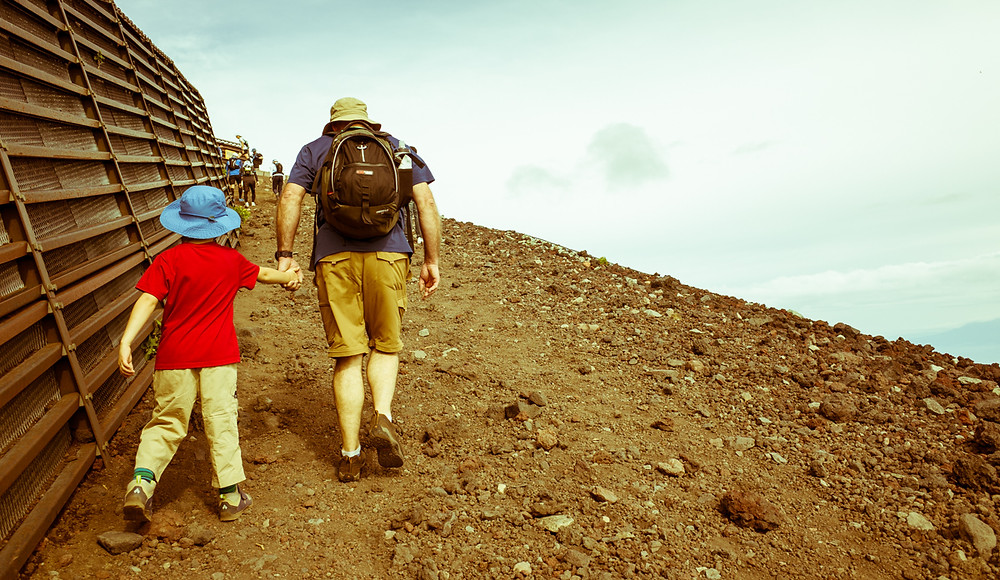 Grandfather assisting grandson on Mt Fuji's Yoshida Trail.