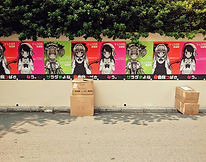 Anime posters along a wall in one of Shibuya's side streets