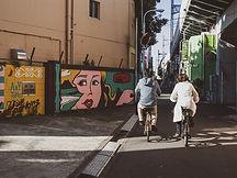 Cycling on mamachari bikes past BnA commissioned street art in Koenji, Tokyo