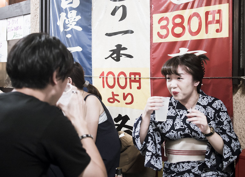 Japanese woman in a yukata enjoying a drink at the Koenji Awaodori Dance Festival.