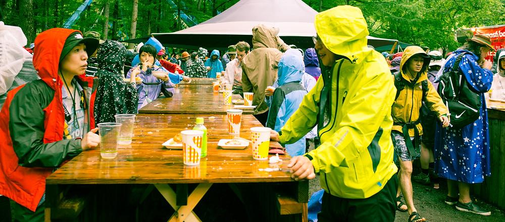 People enjoying a beer in the rain.