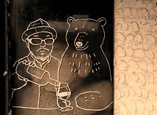 Tokyo street art of a man pouring a bear a beer in a local drinking yokocho