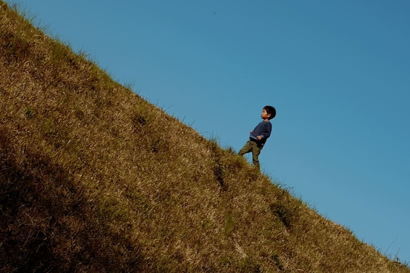 A Japanese boy playing in a grassy field in Tokyo.
