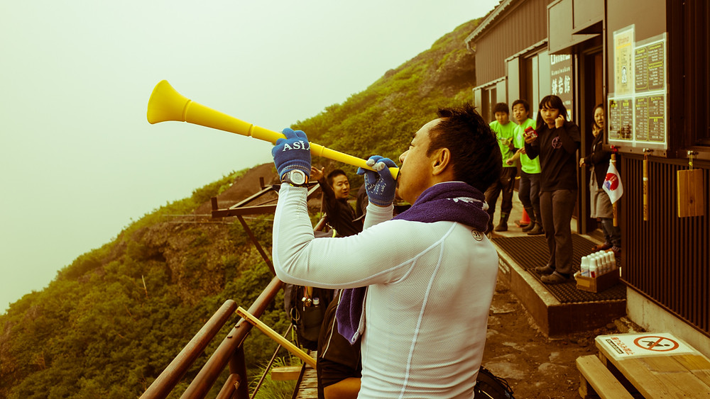 Japanese man playing the vuvuzela on Mount Fuji.