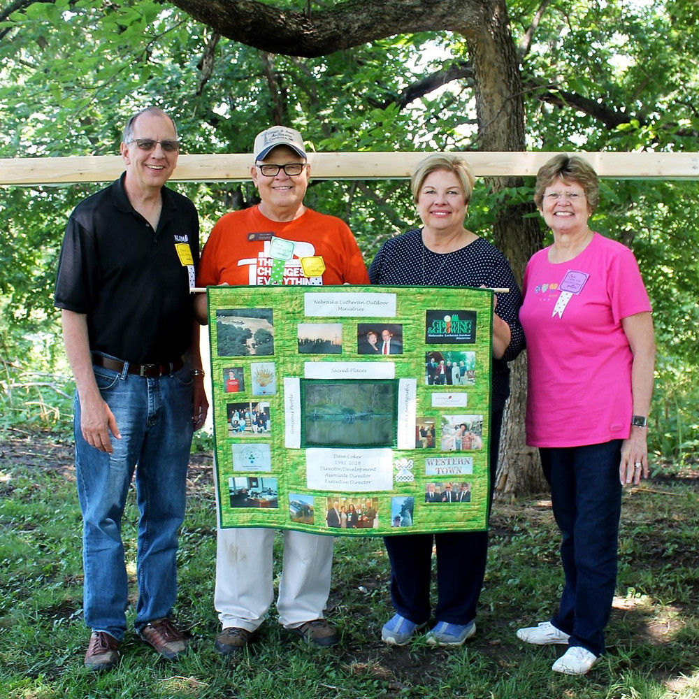 "Dave and Karen Coker hold a memory quilt made and gifted by Caryl and Mark Grorud (also pictured). The quilt was given to Dave and Karen at the Quilt Auction and monetary gifts were accepted from the stage to establish the ""Dave Coker Endowed Camper Fund."""