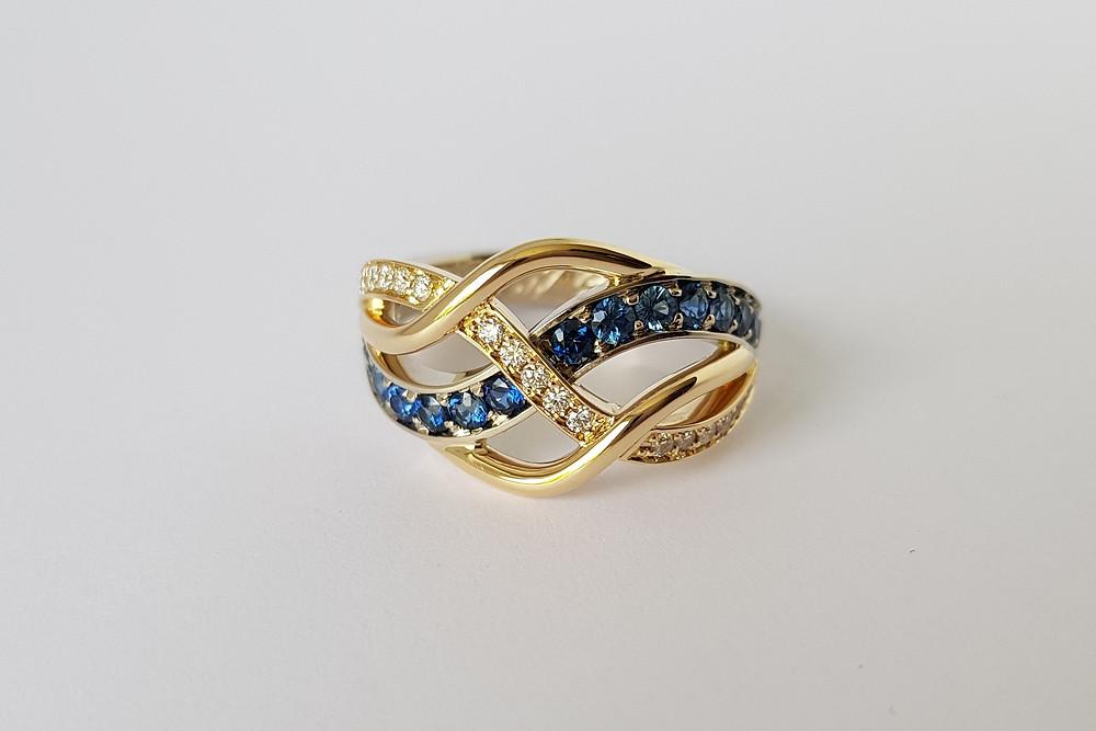 Neparastas formas zelta gredzens ar safīru un briljantu joslām.