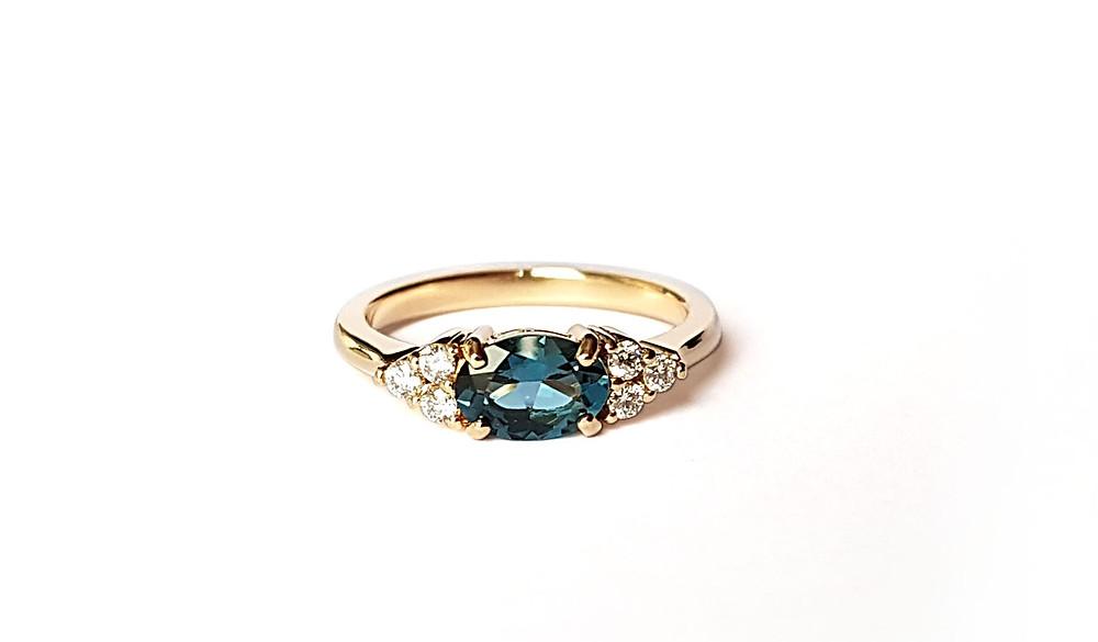 Attēlā elegants saderināšanās gredzenu ar piesātināti zilu safīru, kam sānos izvietoti seši briljantiņi.