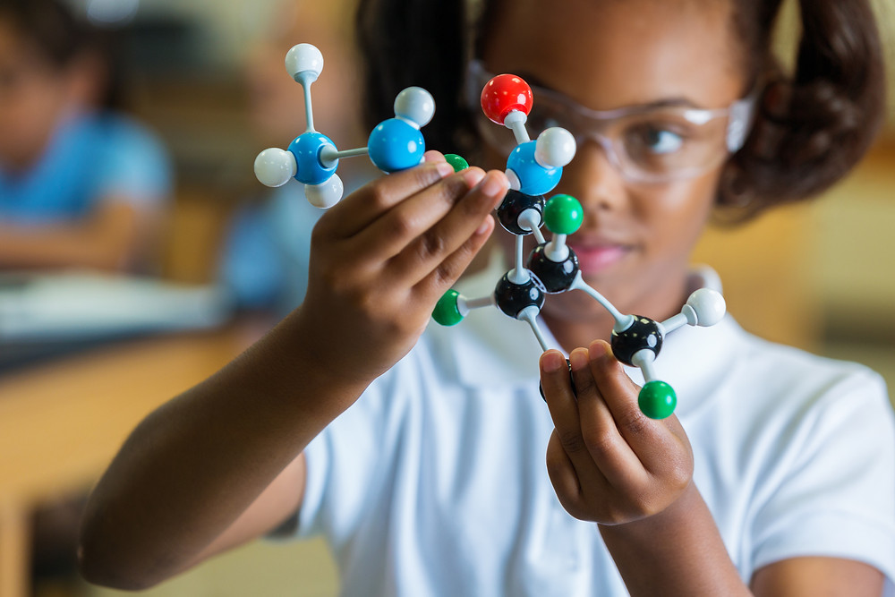 Private elementary school girl examines molecular structure