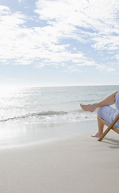 person relaxing on the beach in a beach chair