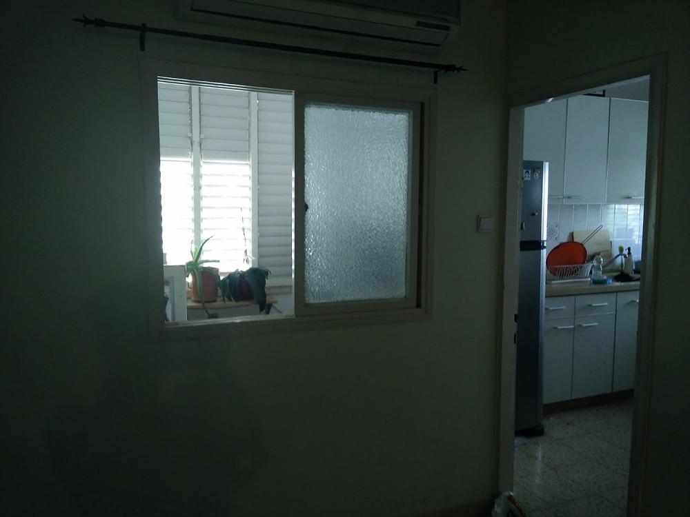 לפני- כניסה למטבח, פינת האוכל מאחוריה מרפסת השירות
