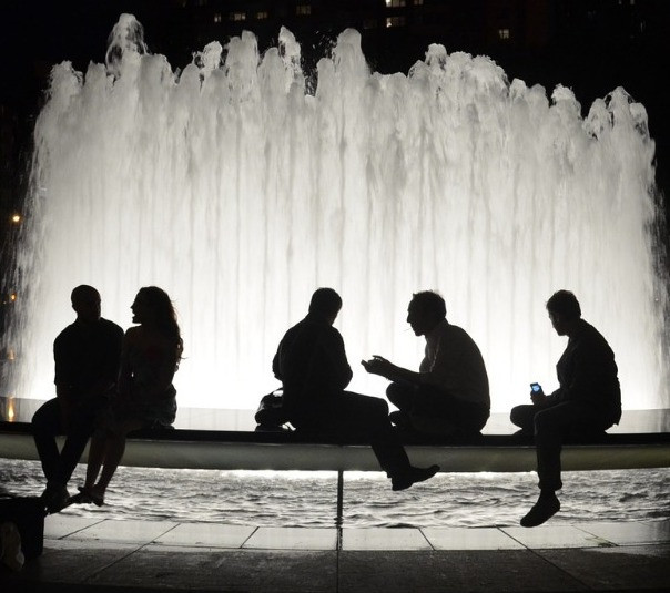 people talking near a fountain