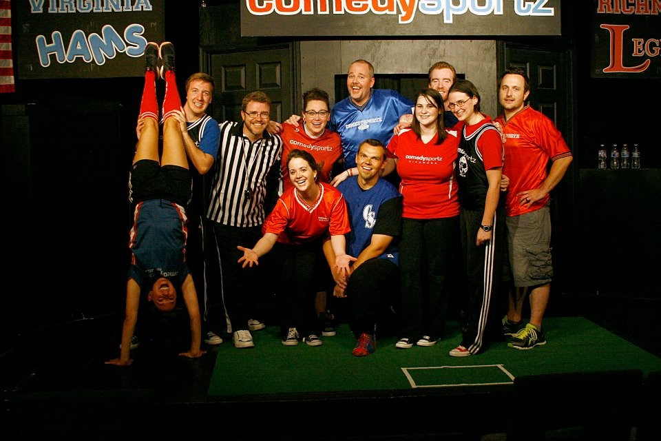 A team of improv players posing on stage