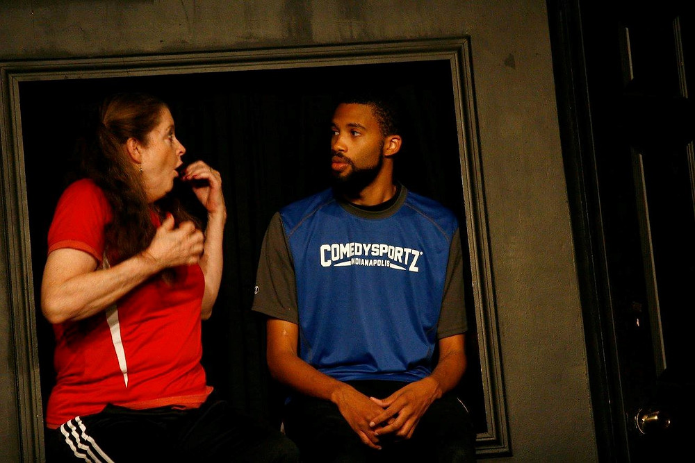 Two improv players performing on stage