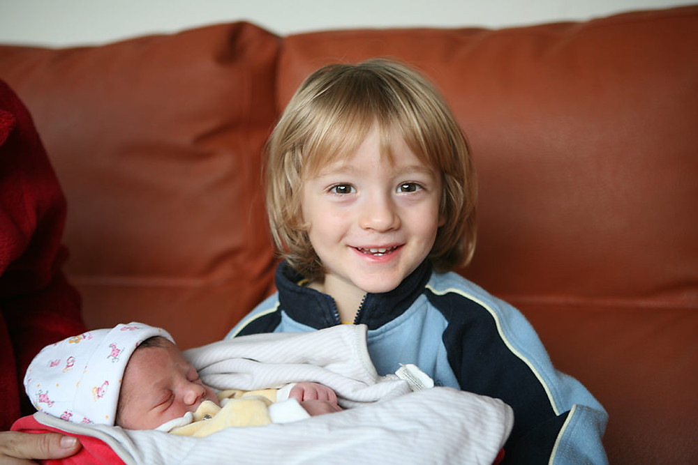 A little boy is smiling with his baby sister in his arms