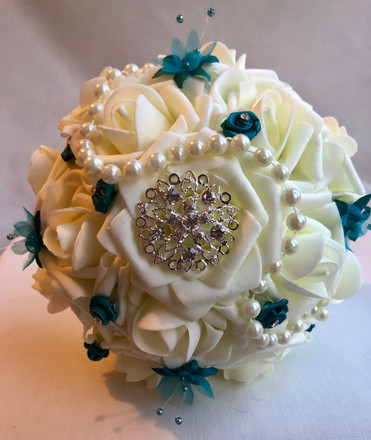 Ivory rose with teal accent, beads and brooches.