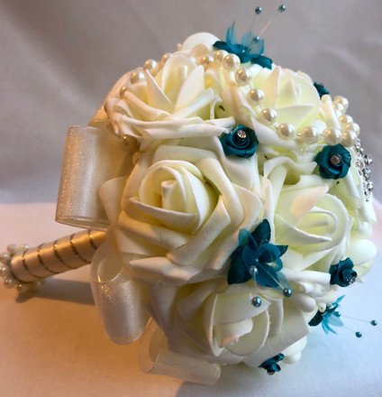 Ivory rose with teal accent and beads.