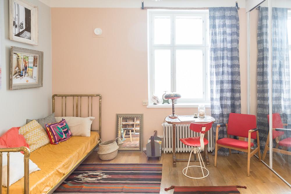 Vintage-tyylisiä kalusteita: sänky, tuoleja, pöytä, lamppu, peilejä, tauluja, matto, ikkuna, ruudulliset ikkunaverhot.