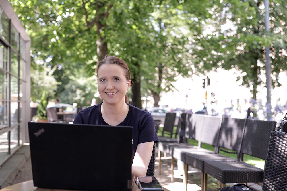 Nainen työskentelee kannettavan tietokoneen kanssa puistokahvilassa aurinkoisessa säässä.
