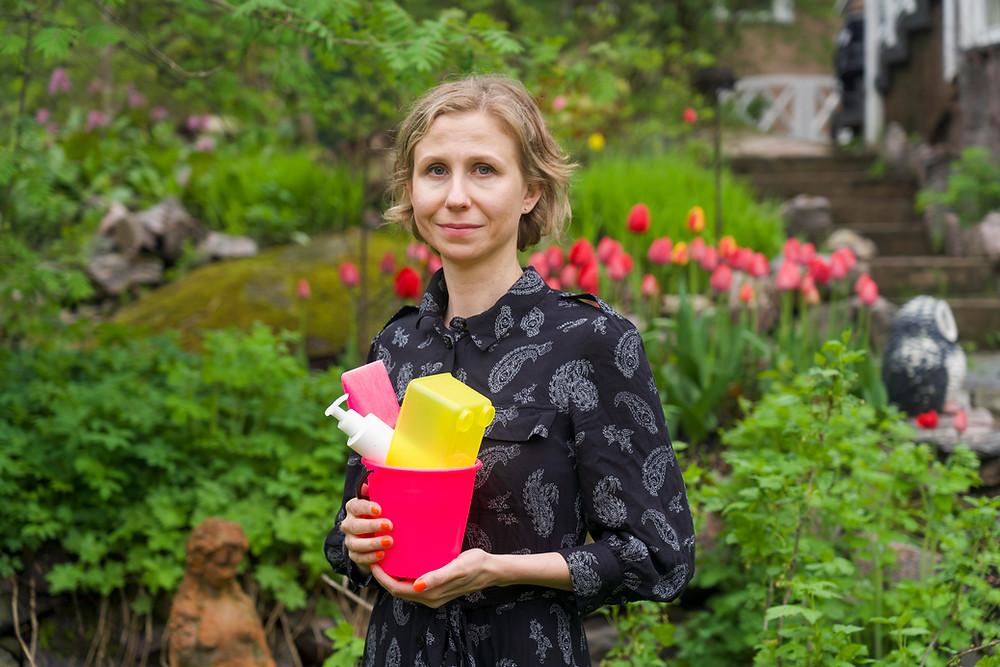 Mona Taponen pitää kukkivassa puutarhassa muoviesineitä käsissään.
