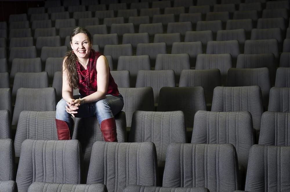 Kati Kallio istuu tyhjässä teatterikatsomossa.