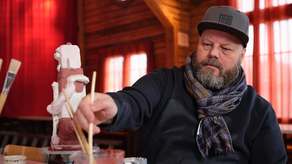 Tuomas Käyhkö työstää taideteosta siveltimellä.