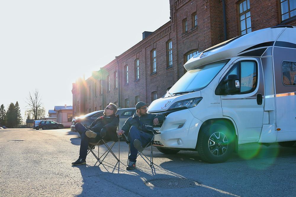 Fabulan kuvaajat istuvat kuvausauton edessä auringonpaisteessa.