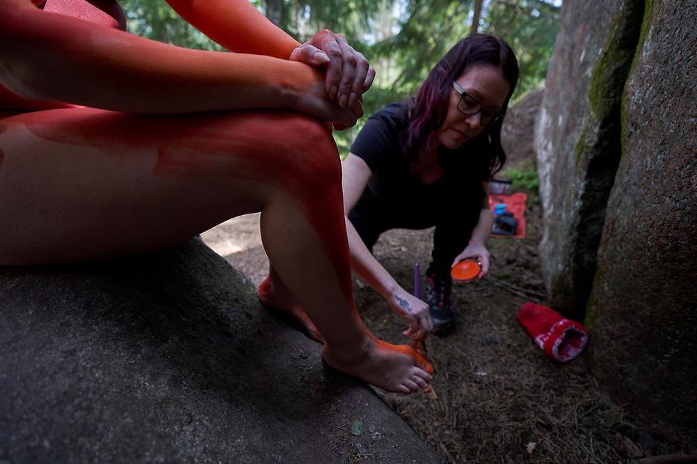 Body painting -taiteilija Riina Laine maalaa mallin jalkoja oranssilla maalilla.
