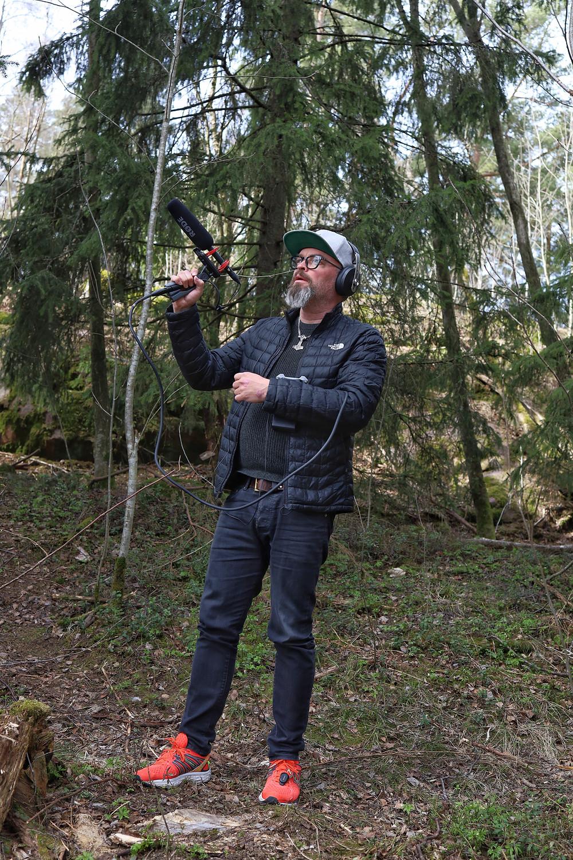 Petri Rajamäki äänittää mikrofonin kanssa metsässä taustaääniä radiomainoksiin.