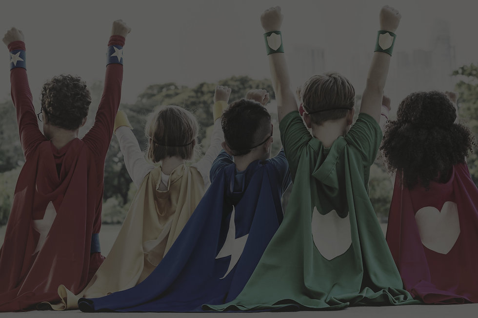 Photo of young children with costume capes on with their hands up to emulate superheroes