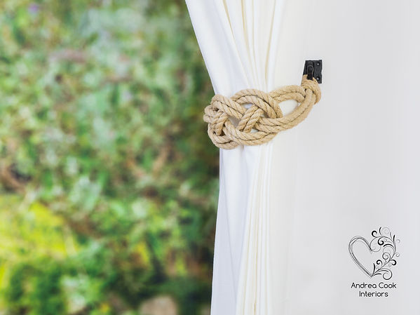 A beige rope double carrick knot curtain tieback on a white curtain.