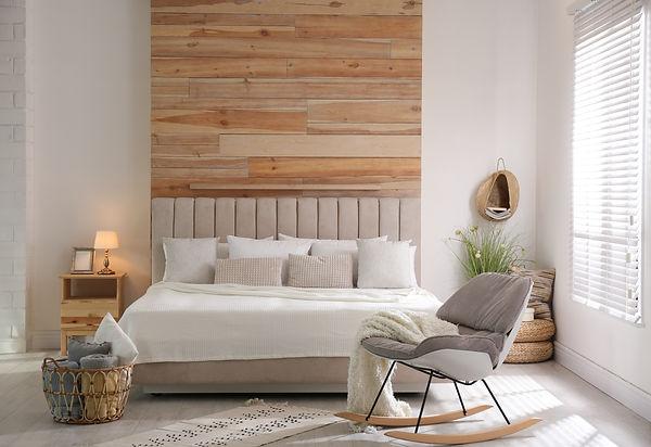 Stylish room interior with big comfortable bed.jpg