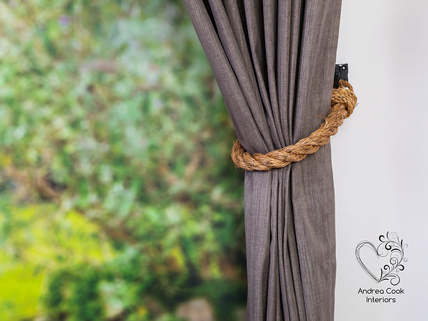 Nautical style curtain holdback made with natural manila rope on a grey curtain.