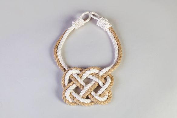 A celtic heart curtain tieback made from beige and white rope