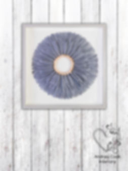 Feather wall art in a circle made of grey feathers mounted on a white wooden shabby chic wall