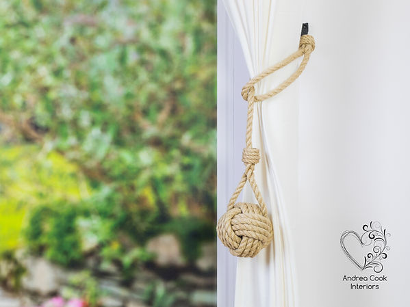 Beige spiliced nautical style curtain tieback witha monkey fist knot on a white curtain