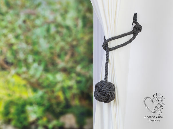 dark grey rope curtain tieback with a monkey fist knot on a white curtain