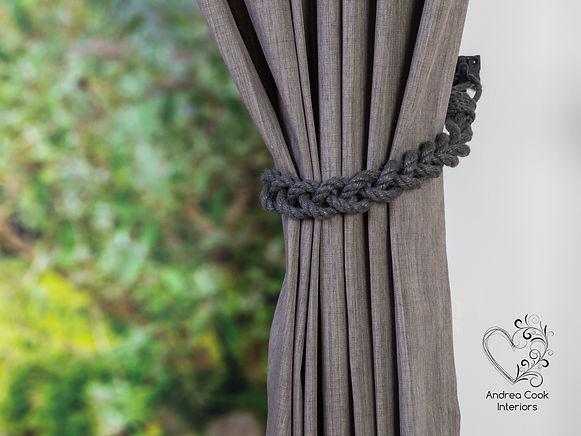 Dark grey handmade braided curtain tieback on a grey curtain