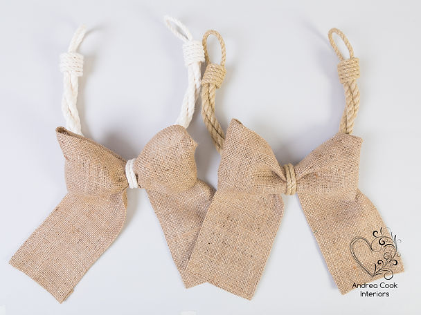 Two handmade curtain tiebacks made with burlap bows. One tieback is beige the other tieback is made from white rope.