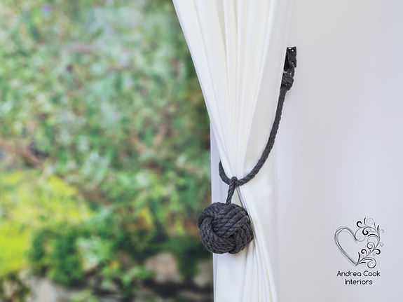 Dark grey curtain tieback on a white curtain