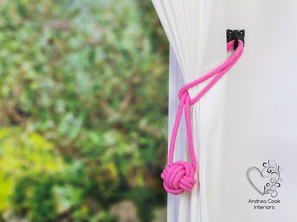 Pink cotton cord monkey fost curtain tieback on a white curtain