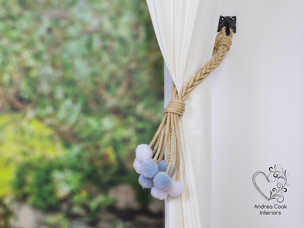 Braided beige rope curtain tieback with grey and white pom poms on a white curtain